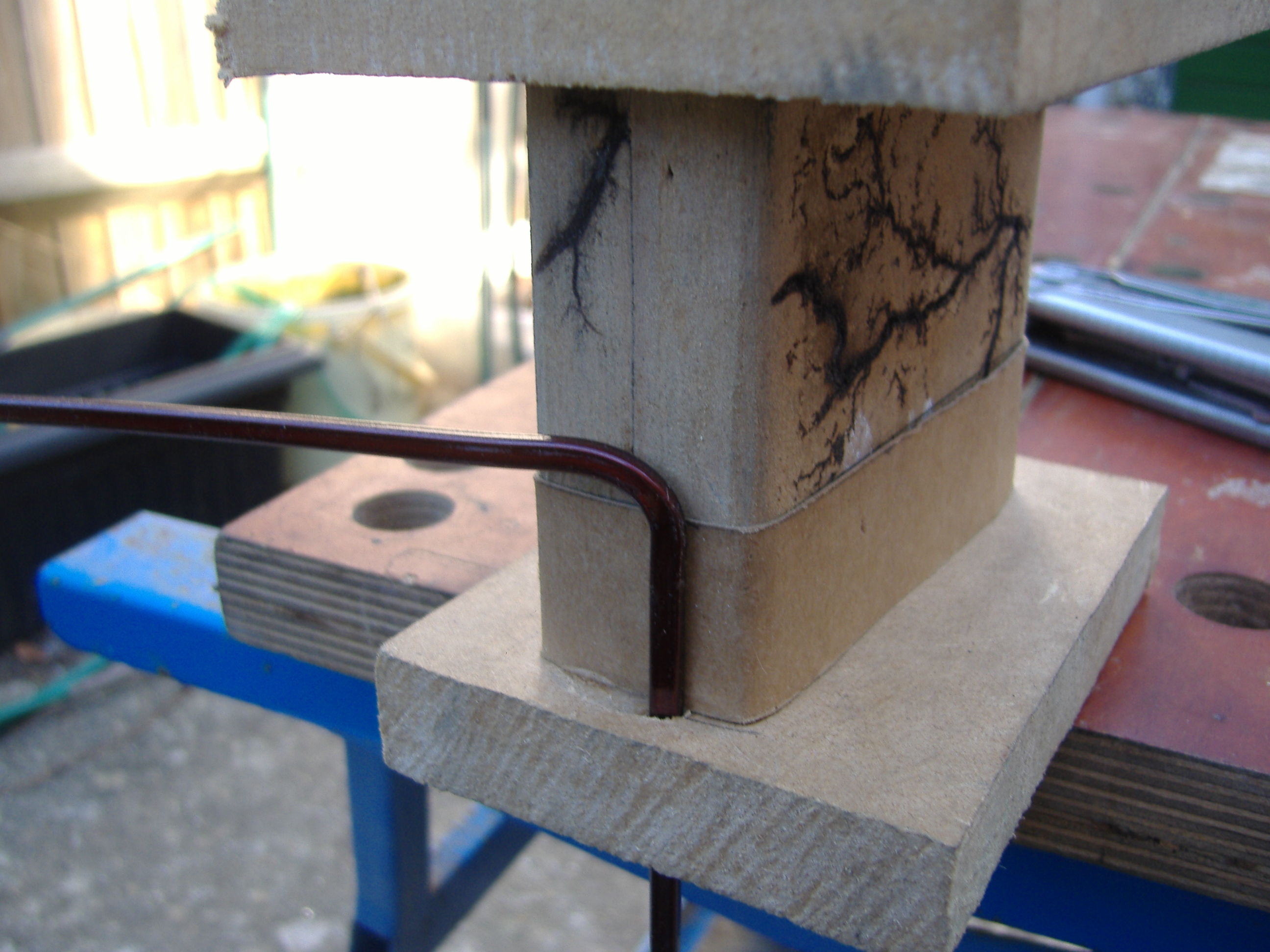 The copper bent and inserted through a hole in the end plate of the former