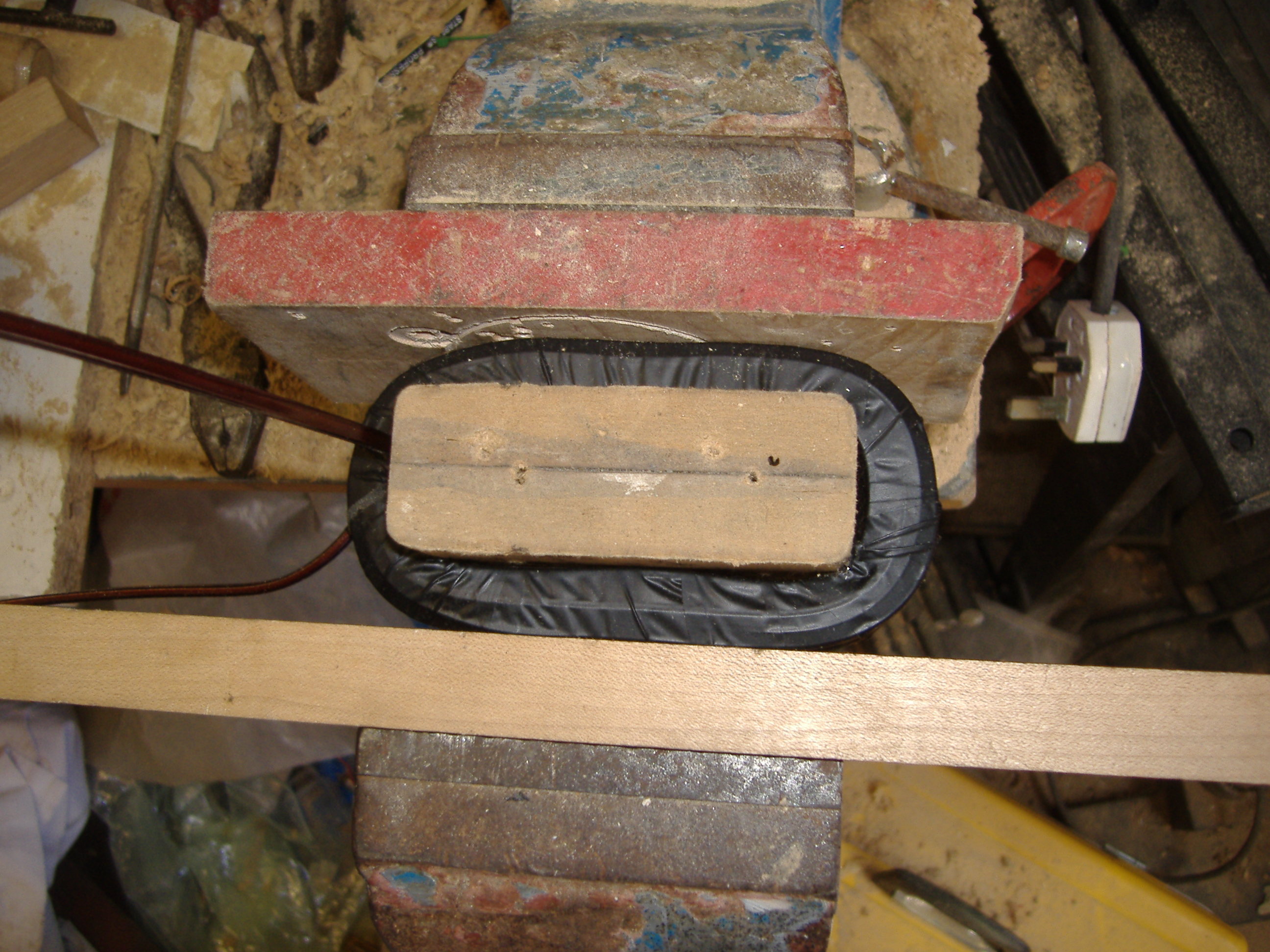 The secondary, wrapped in PVC tape, being squashed in a vice