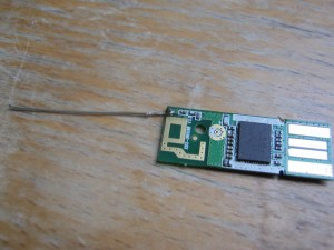 The circuit board from the dongle with a length of jumper wire forming a replacement aerial