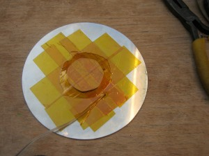 The reverse of the platter, the tape holding the 50p in place is visible, as is the thermocouple junction. It is taped on with kapton tape, where a layer of tape already insulates it from the platter