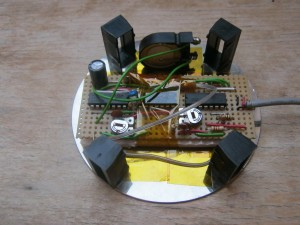 The complete stand pictured from below; the circuit board is in the centre, surrounded by 4 legs and the piezzo transducer off to one side