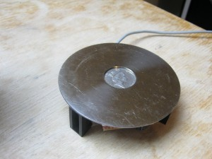 A teapot stand constructed from a HDD platter with a lead snaking out of the back and the edge of a circuit board just about peeking out from underneath